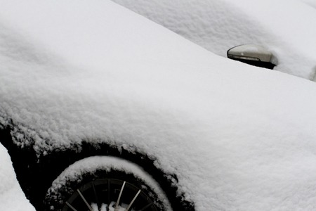 snowscene: Close up of a car covered with snow after snowfall in winter. Copy space for text.