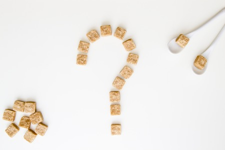 Brown sugar cubes shaped as a question mark on white background. Top view. Diet unhealty sweet addiction diabet concept