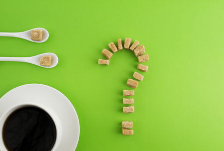Diet, unhealthy sweet addiction concept. White cup of coffee or tea, two spoons and brown sugar cubes as question mark on greenery background. Top view. Flat lay. Copy space for text