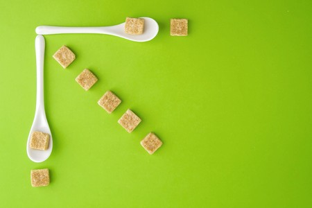 Brown sugar cubes and white spoons on greenery background arringed in rows. Top view. Flat lay. Copy space for text. Diet unhealty sweet addiction concept Stock Photo