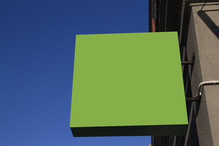 mocked: Greenery mock up. Square shape signboard on wall against blue sky. Stock Photo