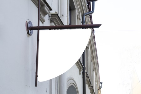 Bespotten. Uithangbord op klassieke bouwmuur.
