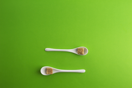 Two white spoons with brown sugar cubes on greenery background. Top view. Copy space for text.