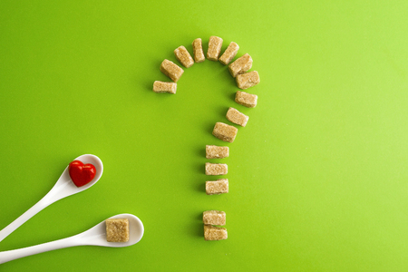 Brown sugar cubes shaped as a question mark over greenery background and two white spoons with heart on one of them. Top view. Diet unhealty sweet addiction concept Stock Photo