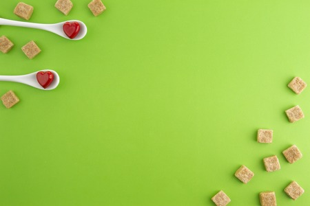 Two white spoons with red hearts on them and brown sugar cubes over greenery background. Top view. Copy space for text. Stock Photo