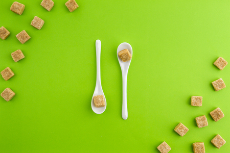 Brown sugar cubes on greenery background with two white teaspoons in the middle. Top view. Copy space for text