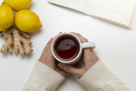 Woman hands holding cup of tea. Near are a book, lemons and ginger on white table. Top view