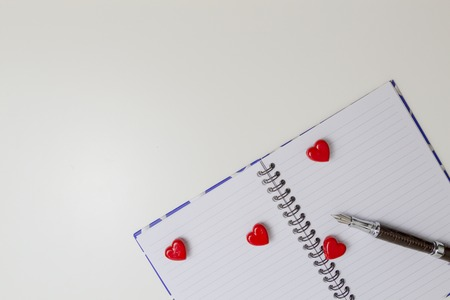 Open notebook with red hearts and pen. Top view. Copy space for text Stock Photo