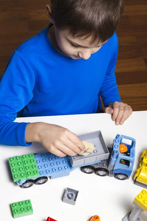 Kleine jongen die met kleurrijke plastic blokken binnen speelt