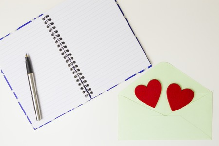 Open notebook, pen, pastel envelope and two red felt hearts on white table. Top view. Stock Photo