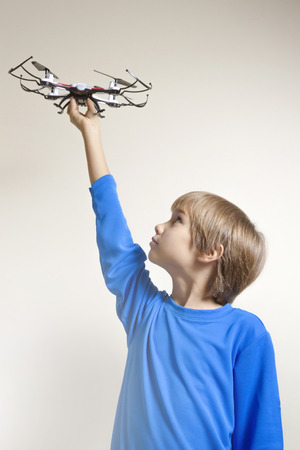 radio activity: Little kid playing with drone. Boy holding quadcopter in his hand, preparing to fly Stock Photo