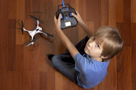 piloting: Little kid is going to play with the quadcopter drone at home. Boy sitting on the floor and holding a radio remote control