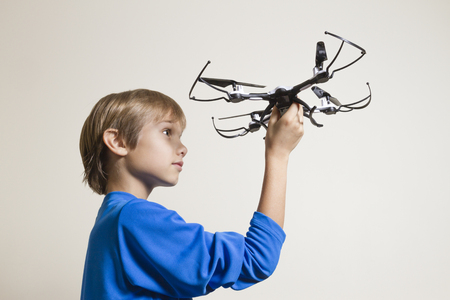 piloting: Little kid holding the drone, preparing for take off