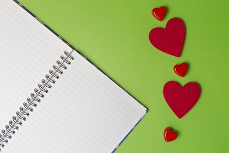 Open notebook and red hearts on greenery background. Valentines day concept. Top view. Copy space Stock Photo