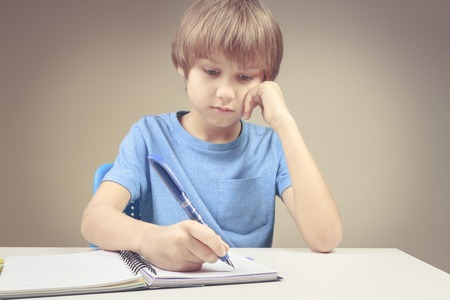 Boy writing on paper notebook. Boy doing his homework exercises Stock Photo