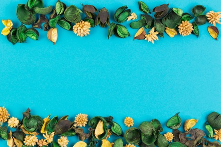 Dried flowers and leaves border frame on blue background. Top view, flat lay. Stock Photo