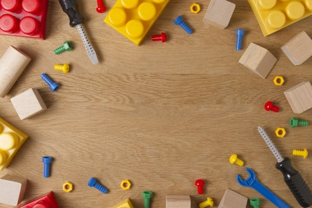 Boys toys frame background. Toy tools, construction blocks and cubes on wooden table. Top view. Flat lay.
