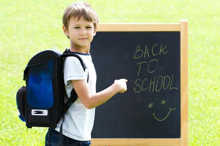 Little schoolboy writting on blackboard. Education, Back to school concept