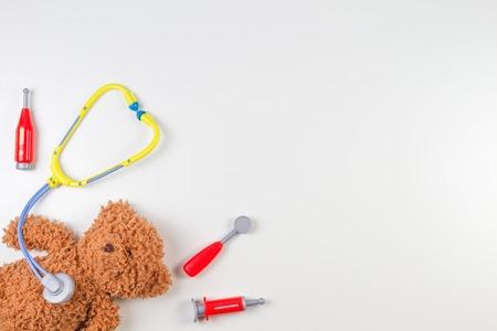 Teddybeer met stuk speelgoed stethoscoop en stuk speelgoed geneeskundehulpmiddelen op een witte achtergrond. Bovenaanzicht Stockfoto