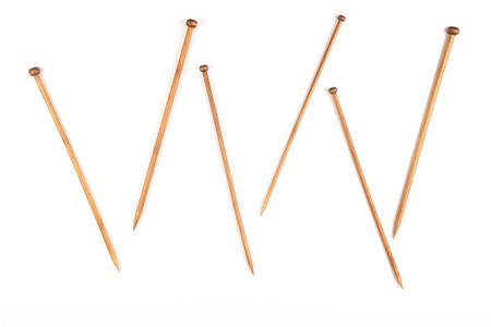 Variety of bamboo knitting needles in different sizes on white background