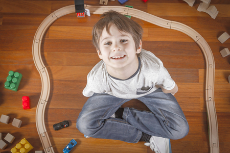 Happy child playing with toys train and railroad while sitting on the wooden floor in his room. Top view