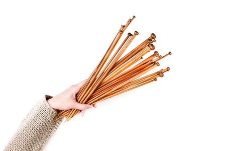 Bunch of brown bamboo wooden knitting needles in woman hand on white background. Top view Stock Photo