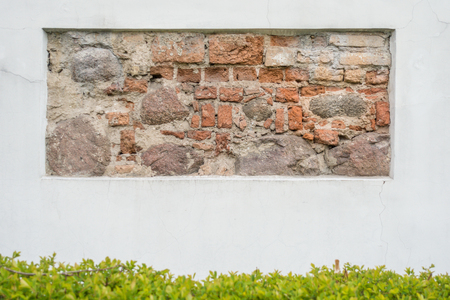 Old stone wall fragment in white plastered wall as background