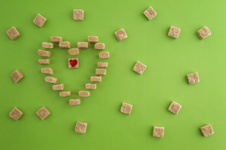 Sugar cubes shaped as heart on greenery background. Top view. Diet unhealty sweet addiction concept
