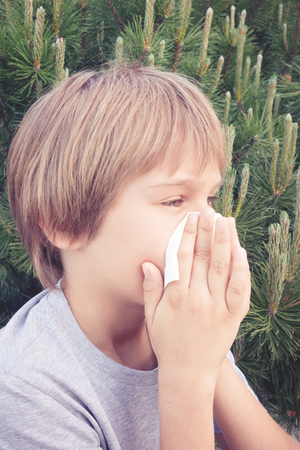 Child blowing nose with tissue paper at the park