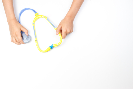 Top view on childs hands with toy stethoscope on a white background.