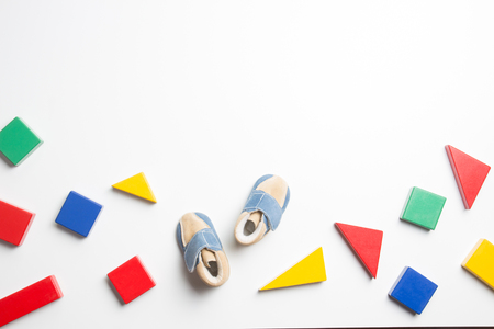 Colorful wooden blocks and baby shoes on white background