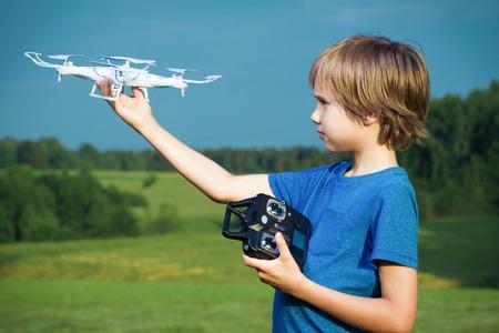 Jongen spelen met drone buitenshuis. Stockfoto - 82047354