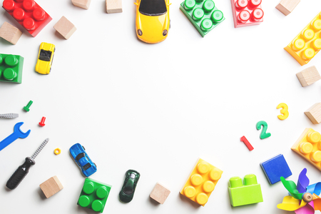 Kids toys frame with construction blocks, cubes, toy tools and cars on white background. Top view.