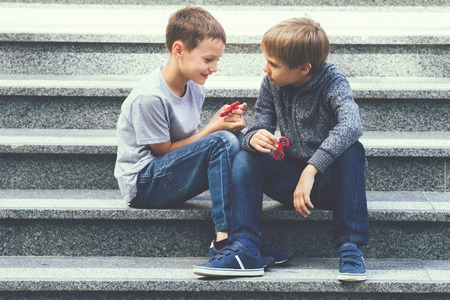 Boys playing with a fidget spinners outdoors