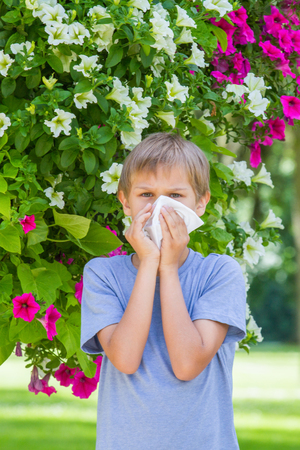 Allergy. Little boy is blowing his nose near tree in bloom.
