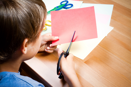Child cutting colored paper with scissors at the table