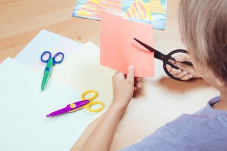 Kind snijden gekleurd papier met een schaar aan de tafel Stockfoto