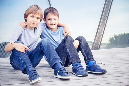 Two happy kids sitting together and embracing Stock Photo