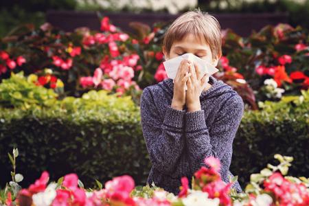 Child having allergy. Boy sitting with tissue in city park