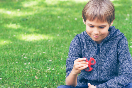 Boy with a fidget spinner outdoors