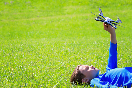 Boy with drone lying on the grass outdoors. Stock Photo