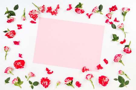 Flowers composition. Frame made of rose flowers. Empty blank paper sheet for text in the middle. Flat lay, top view
