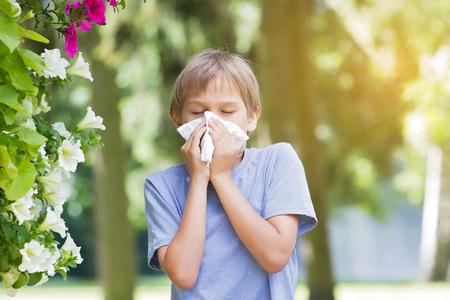 Allergie. Kid blaast zijn neus in de buurt van bloeiende bloemen