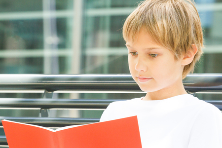 Schoolboy reading books. Kid doing homework outdoors. Back to school concept.