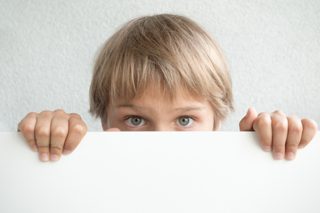 Little boy holding blank white sign or placard hiding his face