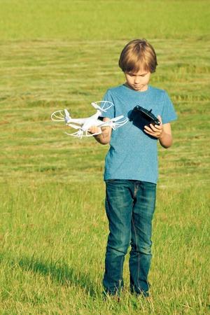 niños jugando videojuegos: Boy playing with drone outdoors.