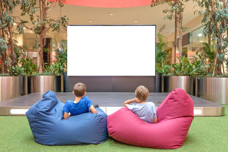 school bills: Mock up. Blank advertising screen in modern shopping mall. Children looking at big blank digital screen