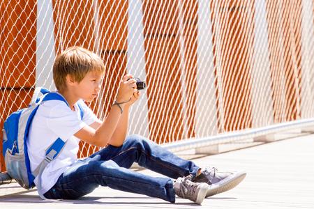Jonge jongenszitting met een digitale camera en het nemen van beelden in de straat