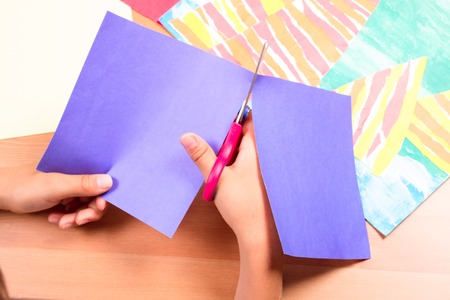 Childs hands cutting colored paper with scissors Stock Photo