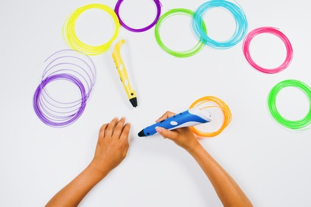 3d printing pens with filaments and kids hands. Top view Stock Photo